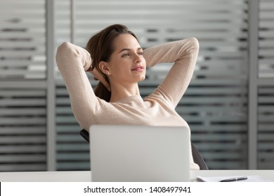 Calm dreamy young businesswoman take break finished work hold hand behind head feel no stress relief at workplace, happy lazy lady enjoy peace of mind business success dreaming sit at desk in office