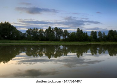 A calm evening landscape by a forest lake. Trees, sky and clouds are reflected in the water