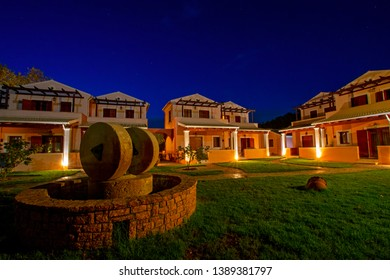 Calm evening on Erikousa island, Greece with beautiful illuminated cottages and green lawn decorated with stone well and ancient millstones under the blue starry sky