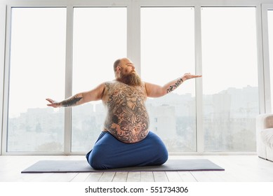 Calm Fat Man Meditating Near Window