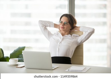 Calm female boss leaning in chair relaxing during work break in office