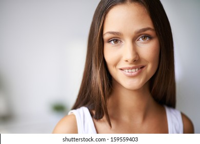 Calm female with dark hair looking at camera with smile