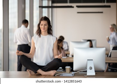 Calm female employee meditate barefoot sitting on office table clearing mind, peaceful millennial businesswoman practice yoga asana in lotus position, exercising with eyes closed in coworking space