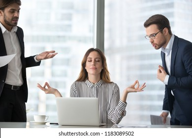 Calm female worker meditate at workplace managing stress not paying attention to angry colleagues, businesswoman sitting in lotus pose practicing yoga staying calm not involved in conflicts or dispute - Shutterstock ID 1183089502