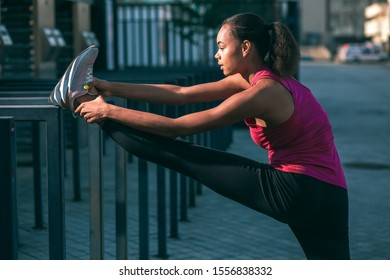 Calm fit woman putting foot on the banister outdoors and bending towards her leg