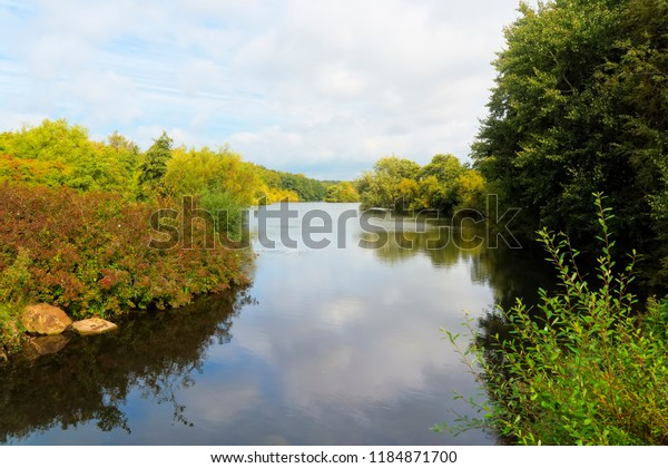 A calm, flat lake twists between banks covered with bushes abd trees. The surface of the lake reflects the weak late summer sky.