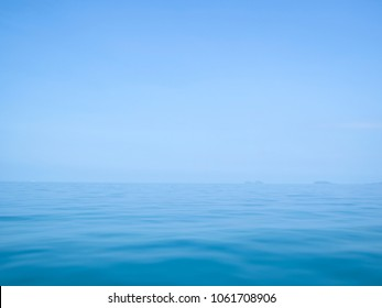calm flat surface of ocean meeting cloudless clear blue sky at horison, in the gulf of thailand between koh samui and ko phangan