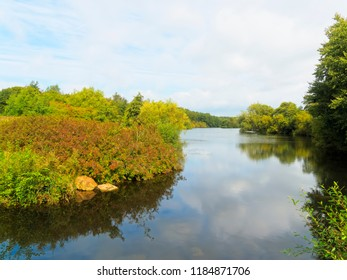 The calm, flat waters of a lake twists between banks covered with bushes abd trees. The surface of the lake reflects the weak late summer sky.