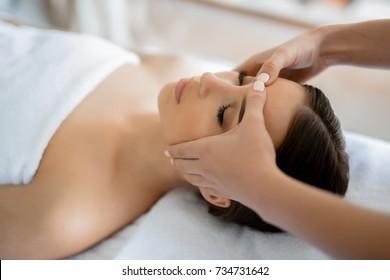 Calm girl having spa facial massage in luxurious beauty salon