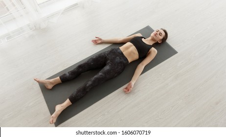 Calm girl relaxing in savasana pose on mat after exercising at home, panorama