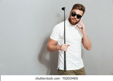 Calm golfer talking by the smartphone and holding club in hand over gray background