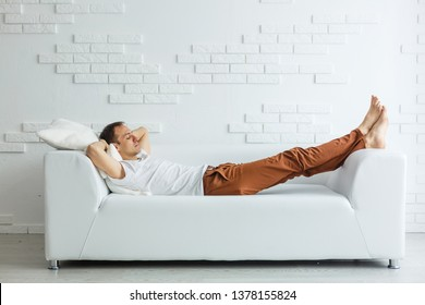 Calm handsome businessman sleeping on couch after work at home
