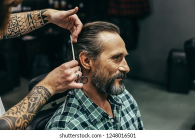 Calm handsome man sitting and smiling while professional barber standing next to him and doing haircut