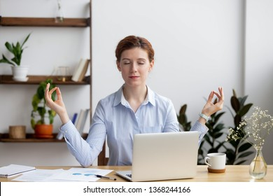 Calm healthy business woman meditate taking break relaxing at office desk feeling balance zen managing reducing work stress relief, mindful employee doing yoga at workplace, peace of mind concept