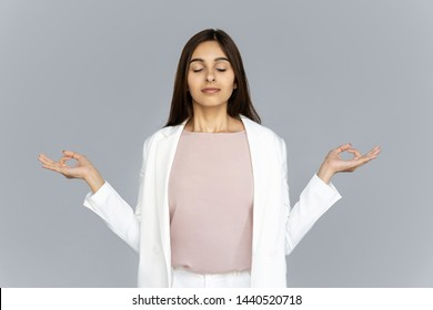 Calm healthy mindful indian business woman wear suit meditating doing yoga exercise with eyes closed breathing fresh air relaxing feel zen no stress free relief isolated on grey studio background