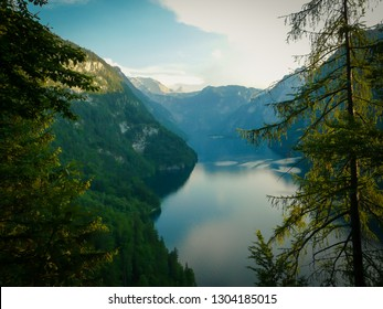 Calm Koenigsee between Alps in Bavaria, Germany with reflections and ducks swimming on the surface. Beautiful summer sunny day by the lake Obersee in Bavarian national park.