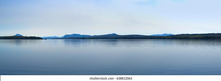 calm lake, blue water and blue sky reflections mountains,  Magog Memphremagog,  Quebec