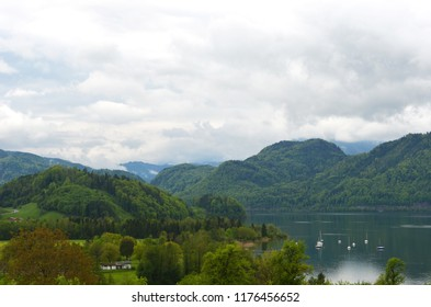 A calm lake lies between forest covered mountains. Some yachts are moored near the shore. A few houses and a road are near the water. The sky is overcast.