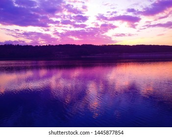 Calm lake on amazing sunrise in purple and blue colors during golden hour. Beautiful nature landscape scenery from boat view.