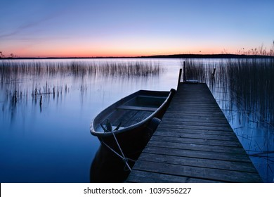 Calm Lake with Reeds at Sunrise, Fishing Boat Tied to Wooden Pier
