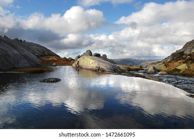 Calm lake with reflection of clouds and blue sky in rocky  Norwegian highlands. Kjerag mountain. Western Norway.