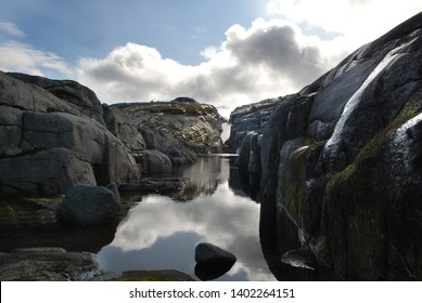 Calm lake with reflection of clouds in rocky gray cliffs  of Norwegian highlands. On the top of Kjerag mountain. Rogaland. Western Norway.