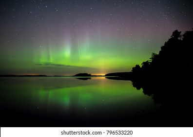 Calm lake reflection with northern lights in Farnebofjarden national park in Sweden.