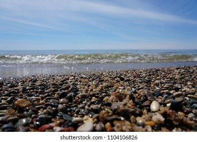 Calm lake with small wave washing on shoreline over pebbles on beach, on bright sunny day