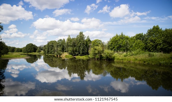 Calm lake water with clouds reflected. Sunny day.