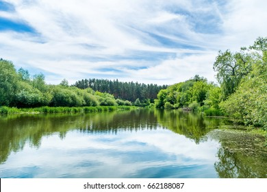 Calm landscape with blue river and green trees