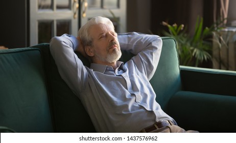 Calm lazy elder senior man having daytime nap relaxing on couch with eyes closed hands behind head, peaceful healthy grandpa sleeping breathing fresh air resting leaning on comfortable sofa at home