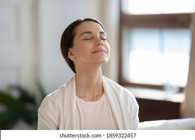 Calm leisure. Content young woman spending time at home alone, sitting on sofa with eyes closed in delight, breathing fresh cool air because of working conditioner, giving face to sunlight from window