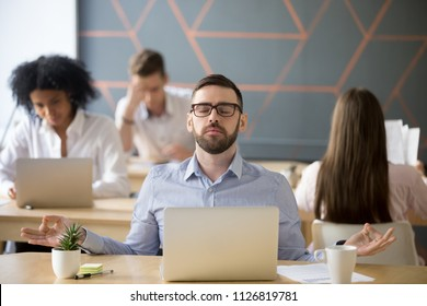 Calm male employee meditating in lotus position, relaxing near laptop in coworking office, peaceful mindful worker practicing yoga at shared workplace, no stress, relieving, controlling emotions