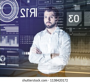 Calm man. Serious attentive computer system analyst standing with his arms crossed and looking at the information on the screen of his futuristic transparent computer