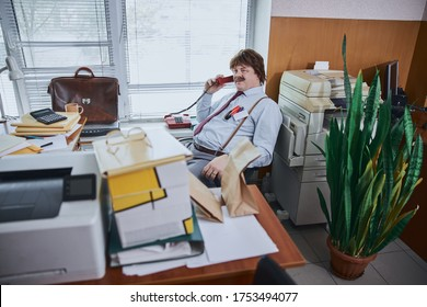 Calm man sitting comfortably on the chair in old-fashioned office and talking on a retro phone