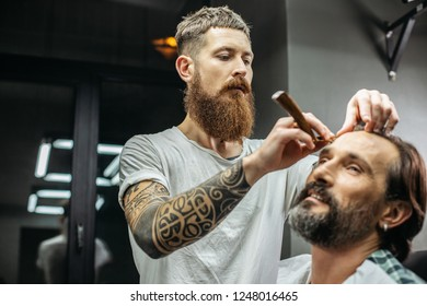 Calm man smiling and professional barber carefully using straight razor while doing haircut