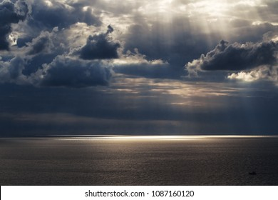 Calm marvelous seascape with beautiful cloudy sky where sun rays are getting through the clouds on the sea