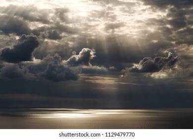 Calm marvelous seascape with wonderful cloudy sky where sun rays are getting through the clouds on the sea