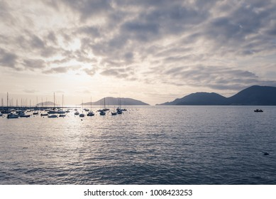 Calm Mediterranean Italian sea view of small harbour with several boats in the distance and mountains in the background at sunset. Vintage matte retro effect.