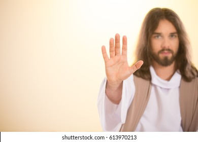 Calm Messiah raising palm of hand, isolated on bright background