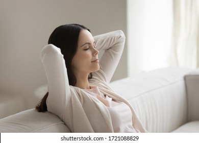Calm millennial Caucasian girl sit relax on cozy sofa at home dream or take nap, peaceful young woman rest on comfortable couch in living room, sleep, relieve negative emotion, stress free concept