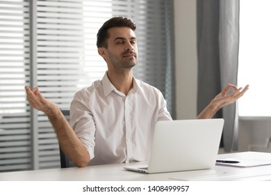 Calm mindful businessman taking break meditate sit at office desk manage work stress free relief resting, healthy serene man doing yoga exercise relax breath fresh air feel peace of mind and zen
