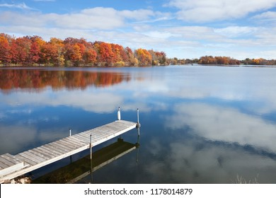 Calm Minnesota lake with a dock and trees in full autumn color under blue sky and clouds