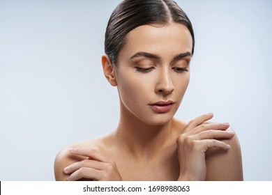 Calm naked graceful lady is standing and touching shoulders. Isolated on white background stock photo