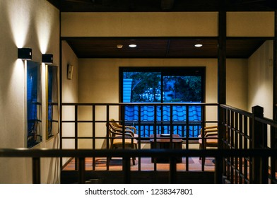 A calm night. A hallway of a very old ryokan in Yufuin Onsen Village where there is a sofa, a table, and a chair made of wood.