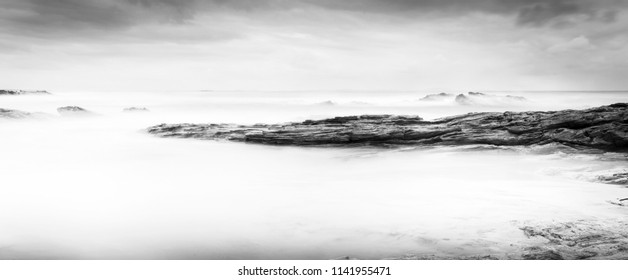 Calm ocean landscape time-lapse with smooth waves and rocks in black and white