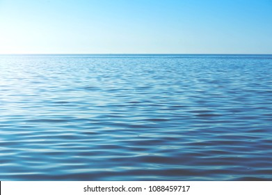Calm ocean water background. Blue waves of soft surface of the sea. Horizon of the sea. Abstract pattern
