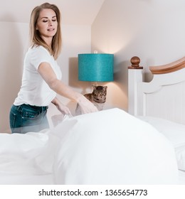 Calm ocicat cat watching his owner making her bed in the morning. Middle aged woman in blurred motion doing her morning routine.