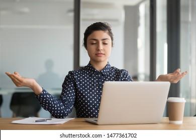 Calm office worker hindu woman sit at desk near laptop folded fingers mudra gesture take break resting at workplace do yoga exercise practise breath technique reduce stress, no anxiety at work concept