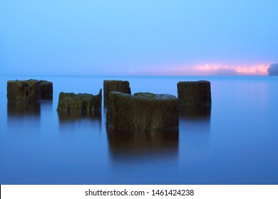 Calm on the river. Industrial piles
